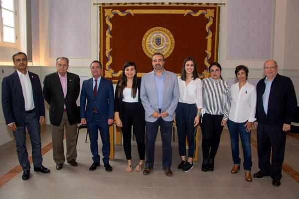 Foto de familia del Rector Robaina y el Vicerrector Peñate, junto con las alumnas becadas y los organizadores