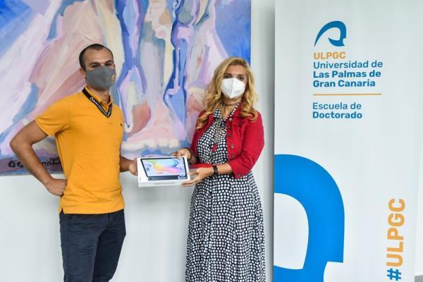 la directora de la Escuela de Doctorado hace entrega de un premio al ganador del concurso HiloTesis